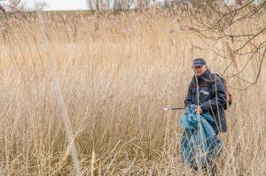 Man zoekt afval in de natuur. Boswachters vinden steeds vaker gedumpt afval.