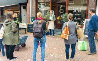 mensen krijgen uitleg bij winkel bij zero waste wandeltours
