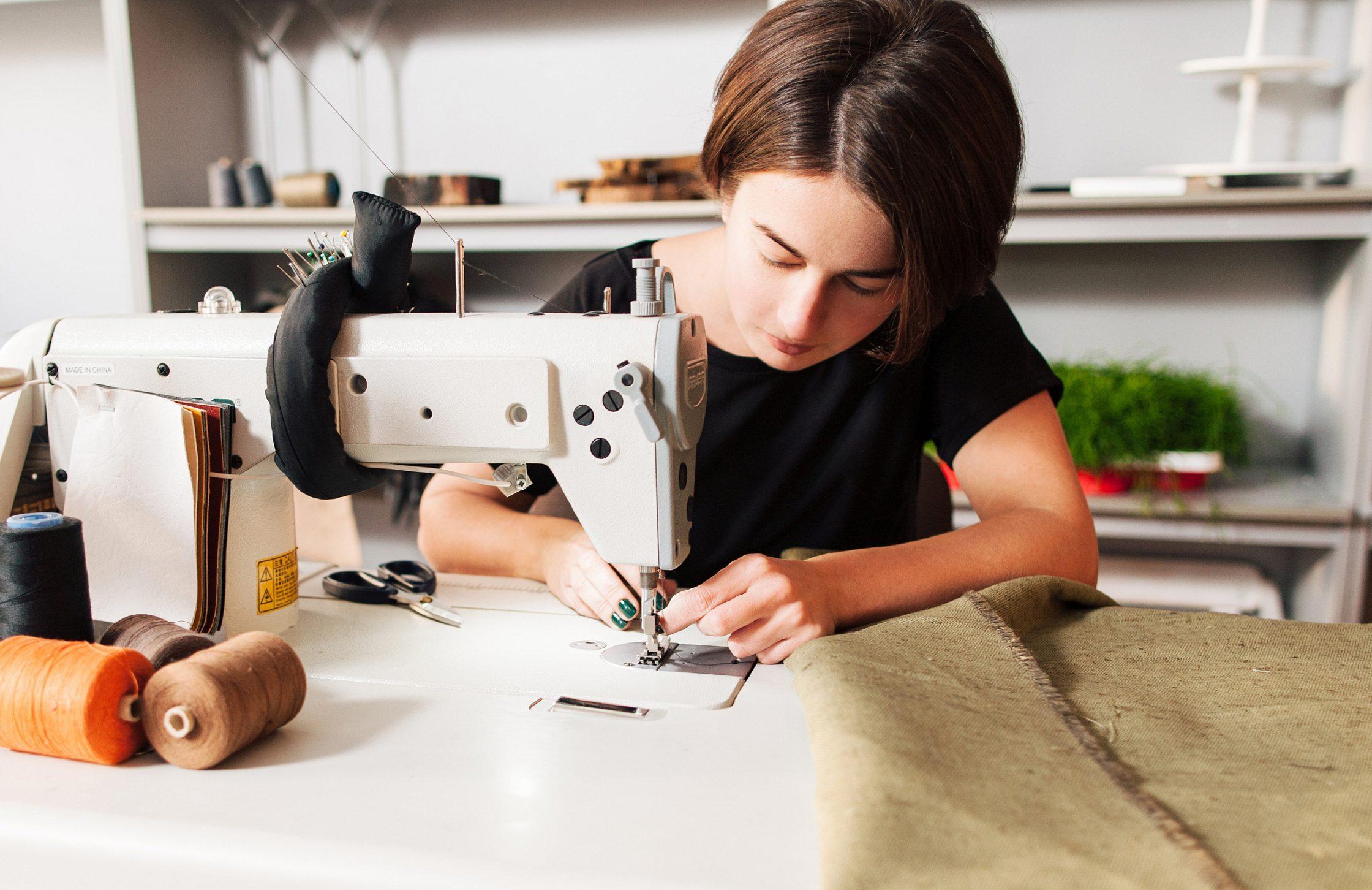 meisje repareert kleding met naaimachine