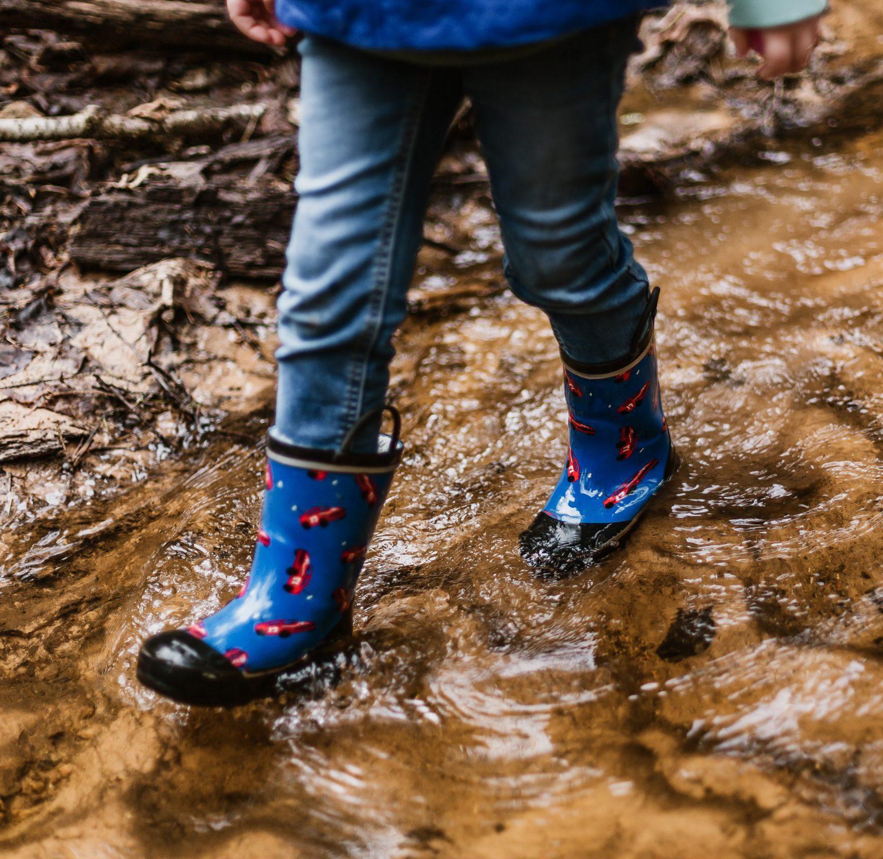 kind loopt met laarzen door water