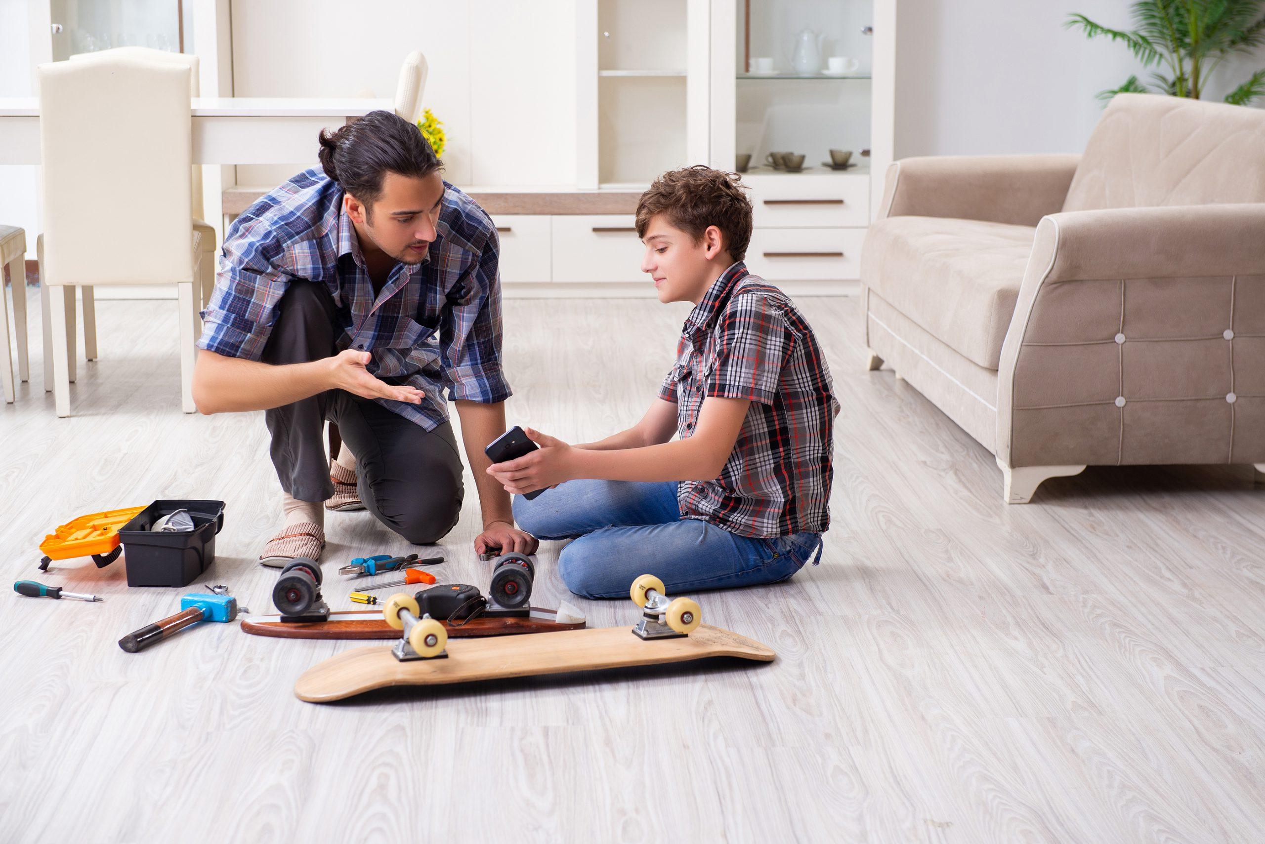 vader repareert skateboard met zoon