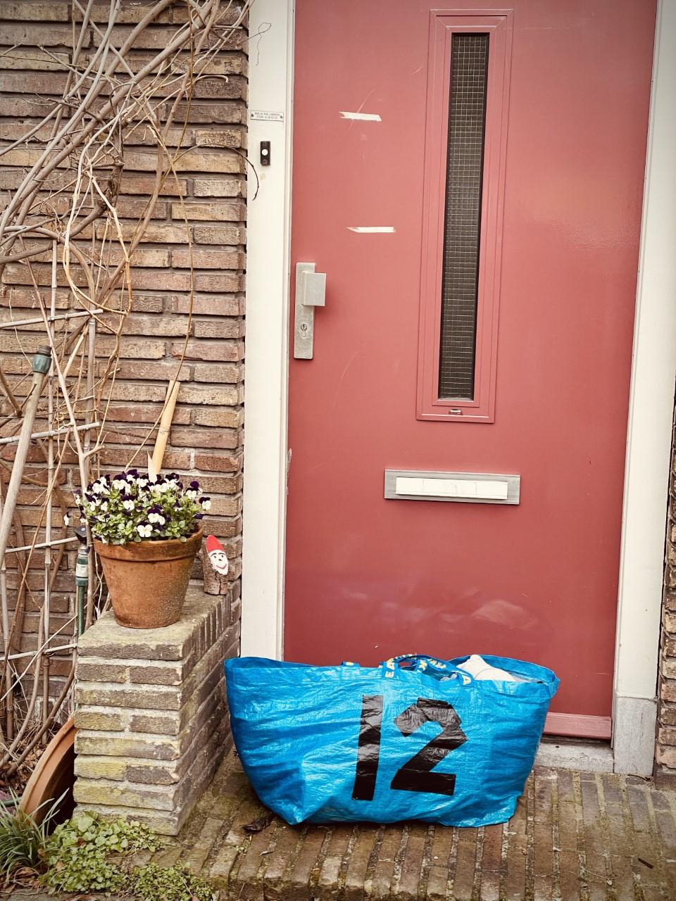 tas met kleding bij voordeur