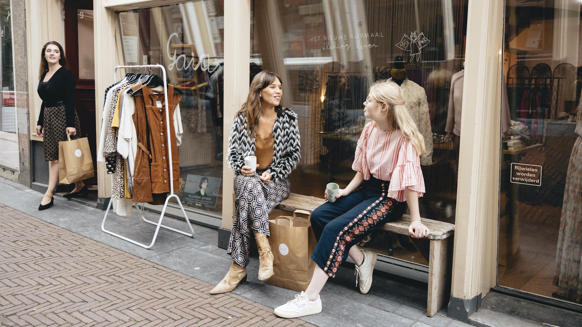 twee vrouwen zitten op bankje voor kledingwinkel