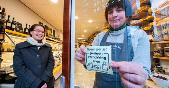 vrouw plakt zero waste sticker op ruit