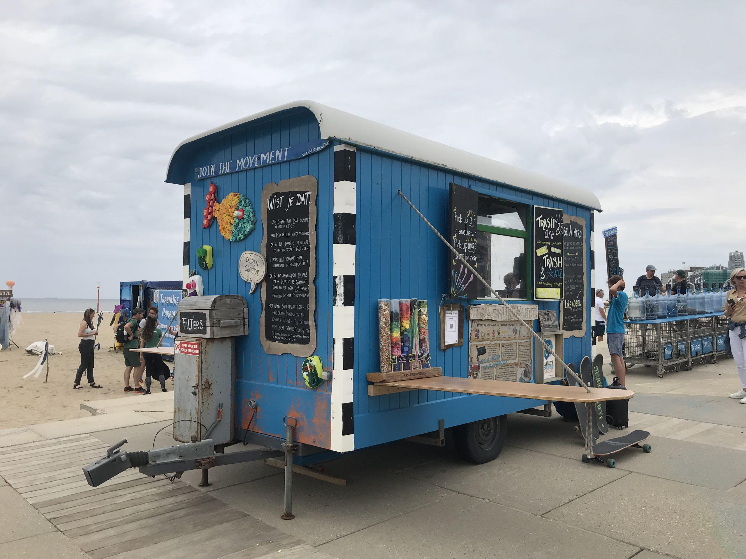 blauwe pipo-wagen op het strand van TrashUre Hunt